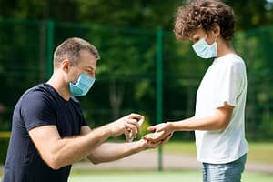 Dad in face mask using sanitizer with his son